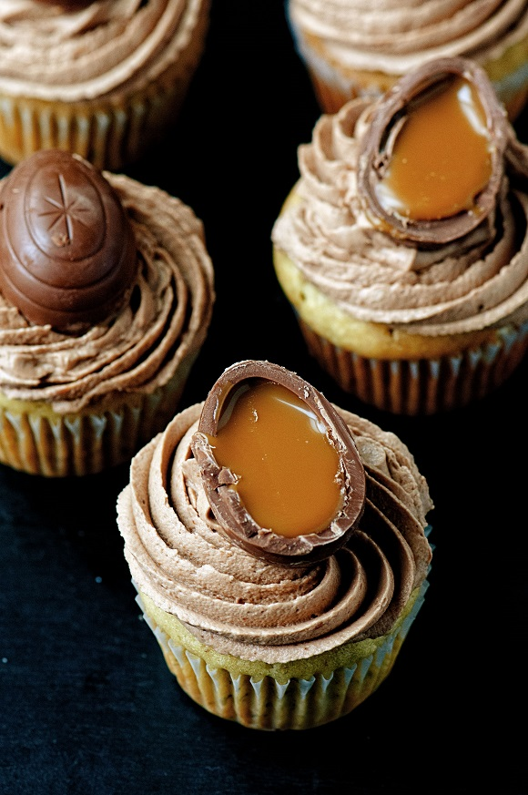 Five banana cupcakes with the caramel eggs dripping down the cupcake.