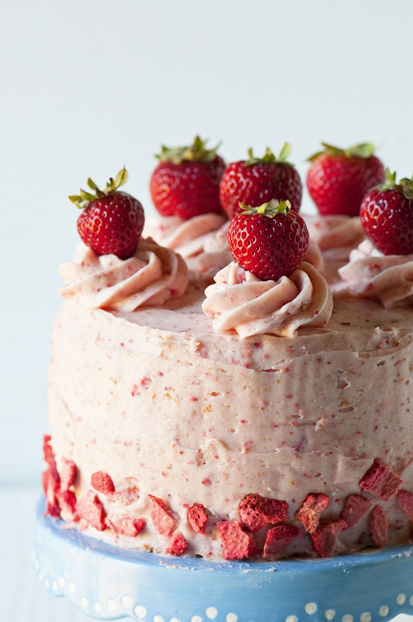 Side view of Strawberry Shortcake Layer Cake with close up of the strawberries on top of the cake.