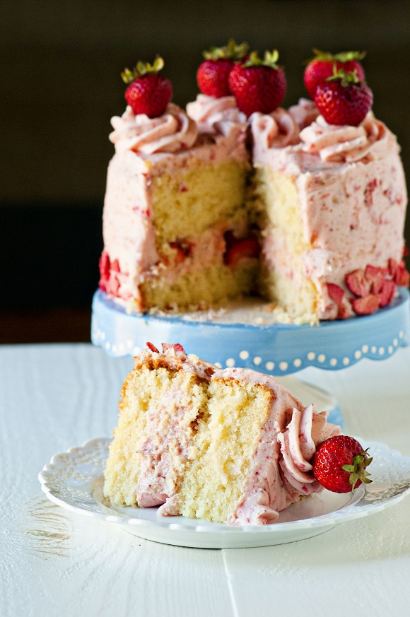 Slice of Strawberry Shortcake Layer Cake with cake in the background.