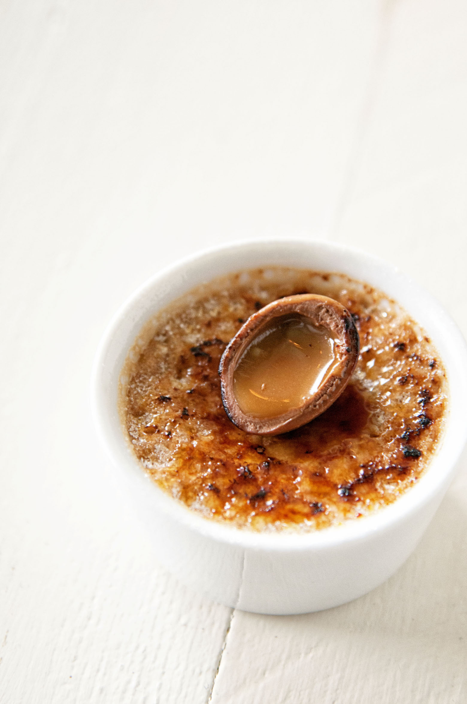 Creme brulee with caramelized top and a mini cadbury egg sliced open on top with the carmel spilling out.