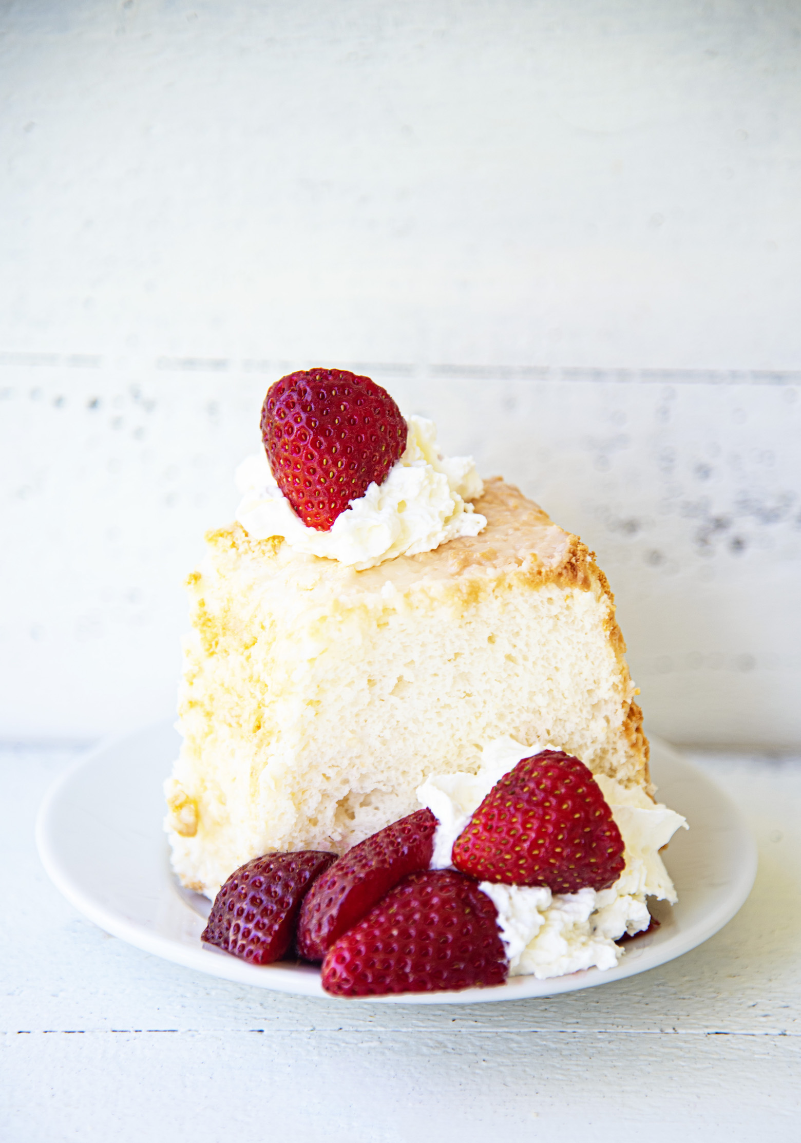 Slice of Key Lime Angel Food Cake with whipped cream and strawberries
