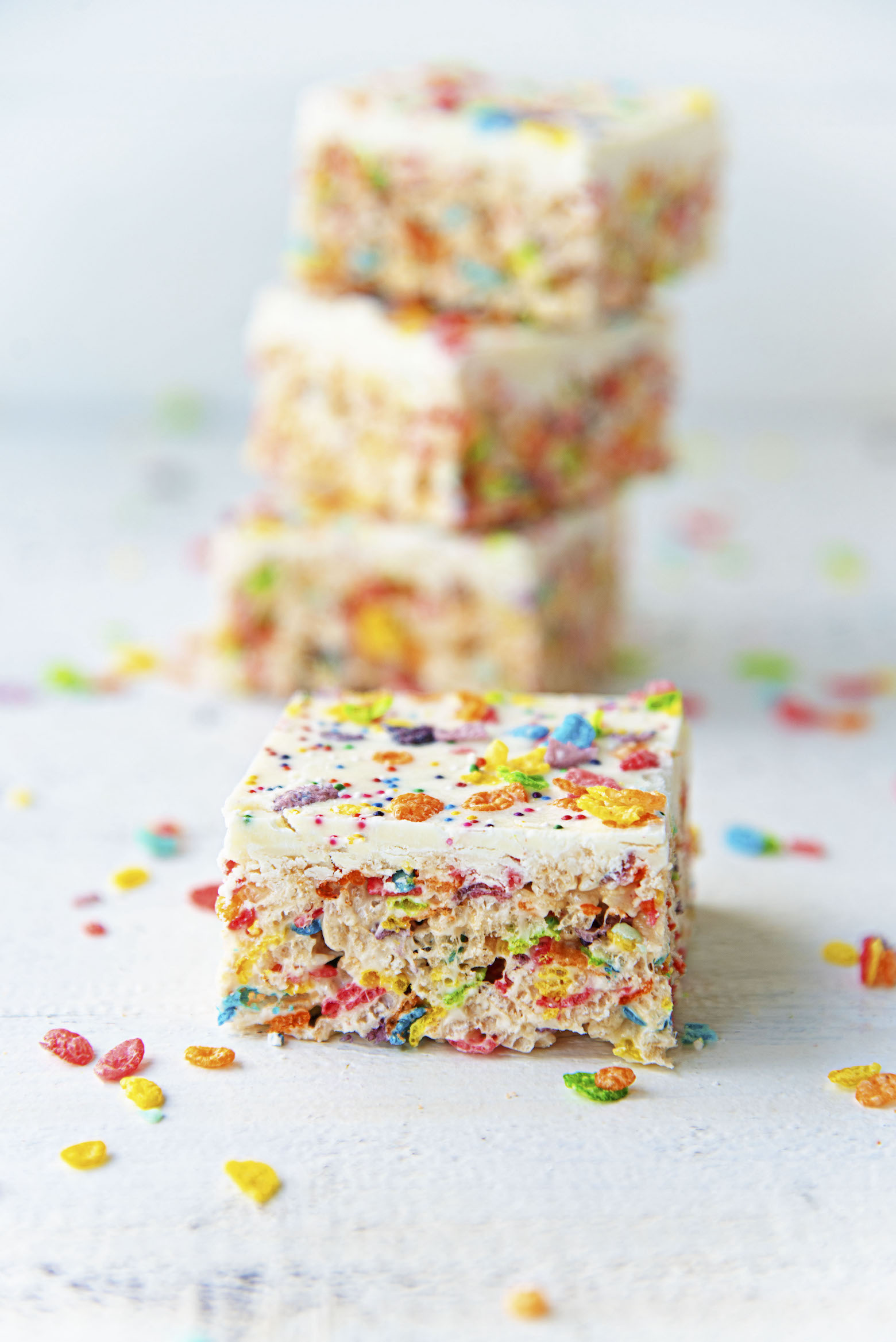 White Chocolate Fruity Pebbles Marshmallow Treats stacked up.