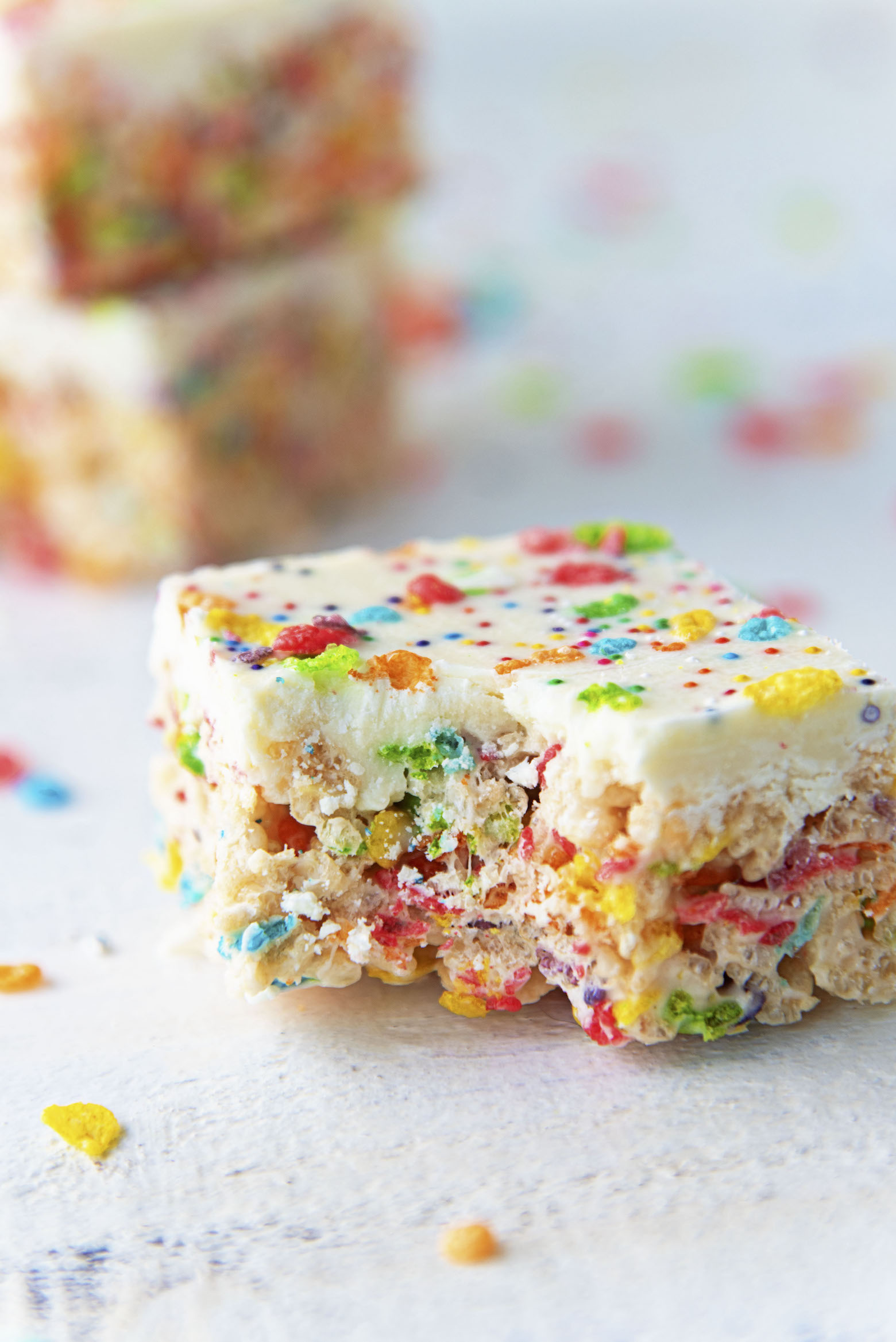 White Chocolate Fruity Pebbles Marshmallow Treats with bite out of them.