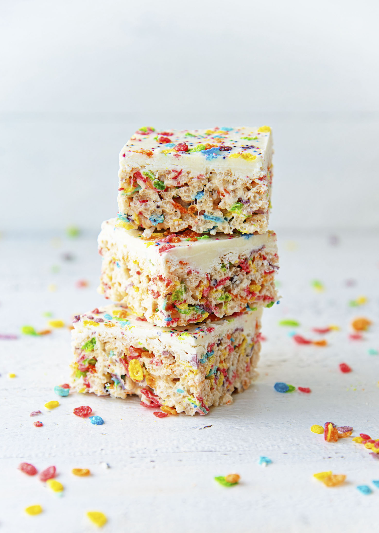 White Chocolate Fruity Pebbles Marshmallow Treats stacked in three.