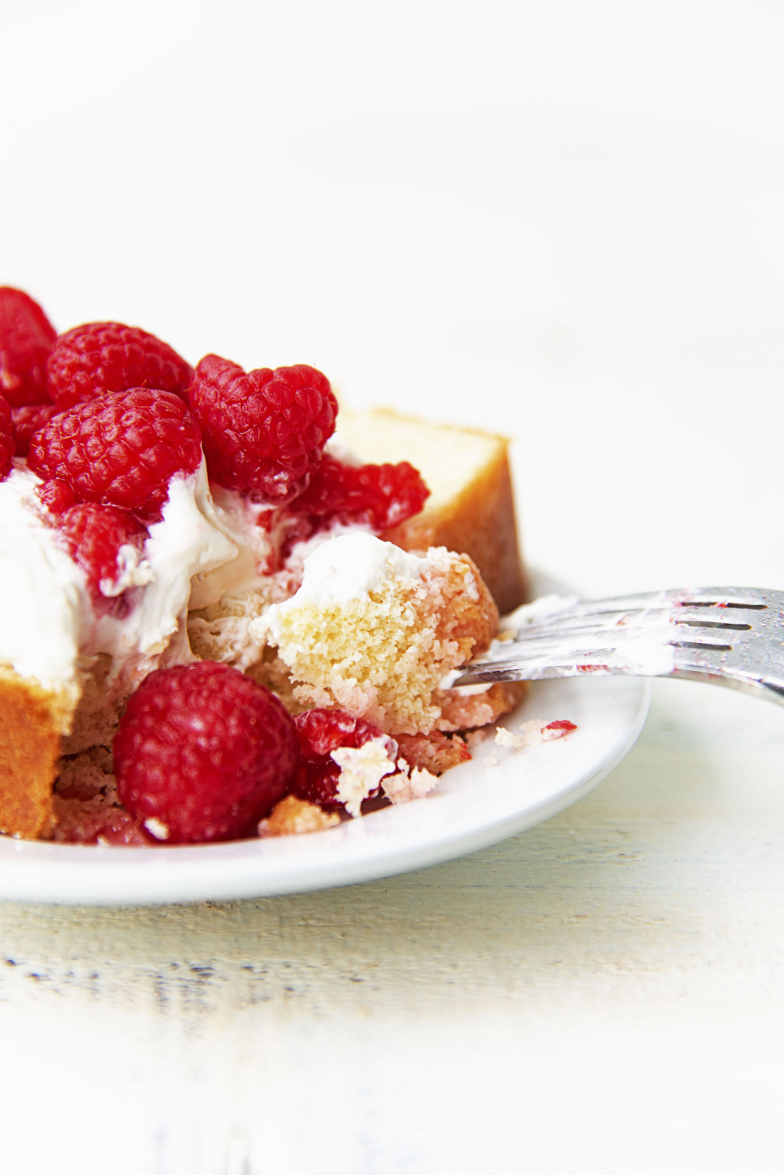 Vanilla Butter Loaf Cake with whipped cream and berries with a fork taking out a bite.