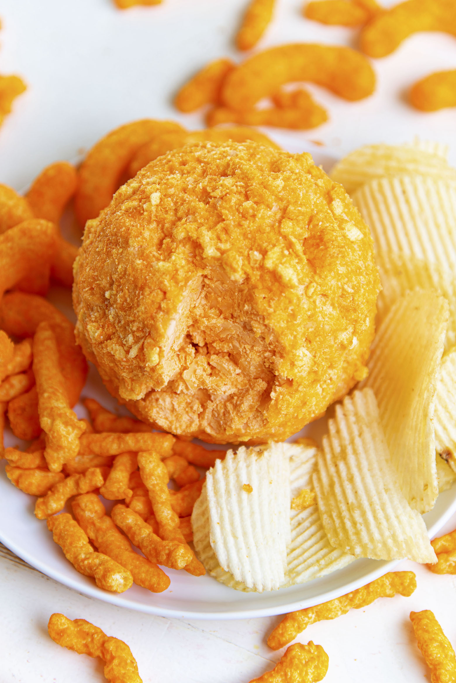Three quarter shot of Cheetos Three Cheese Cheeseball with piece cut out.