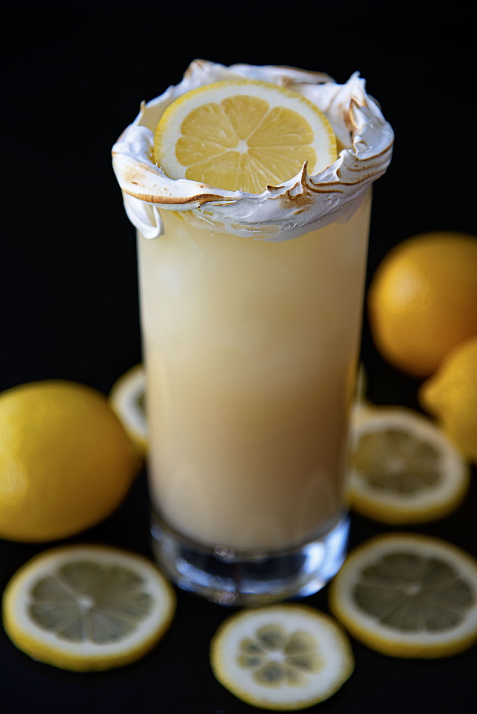 Full shot of the cocktail with fresh lemons around the glass.