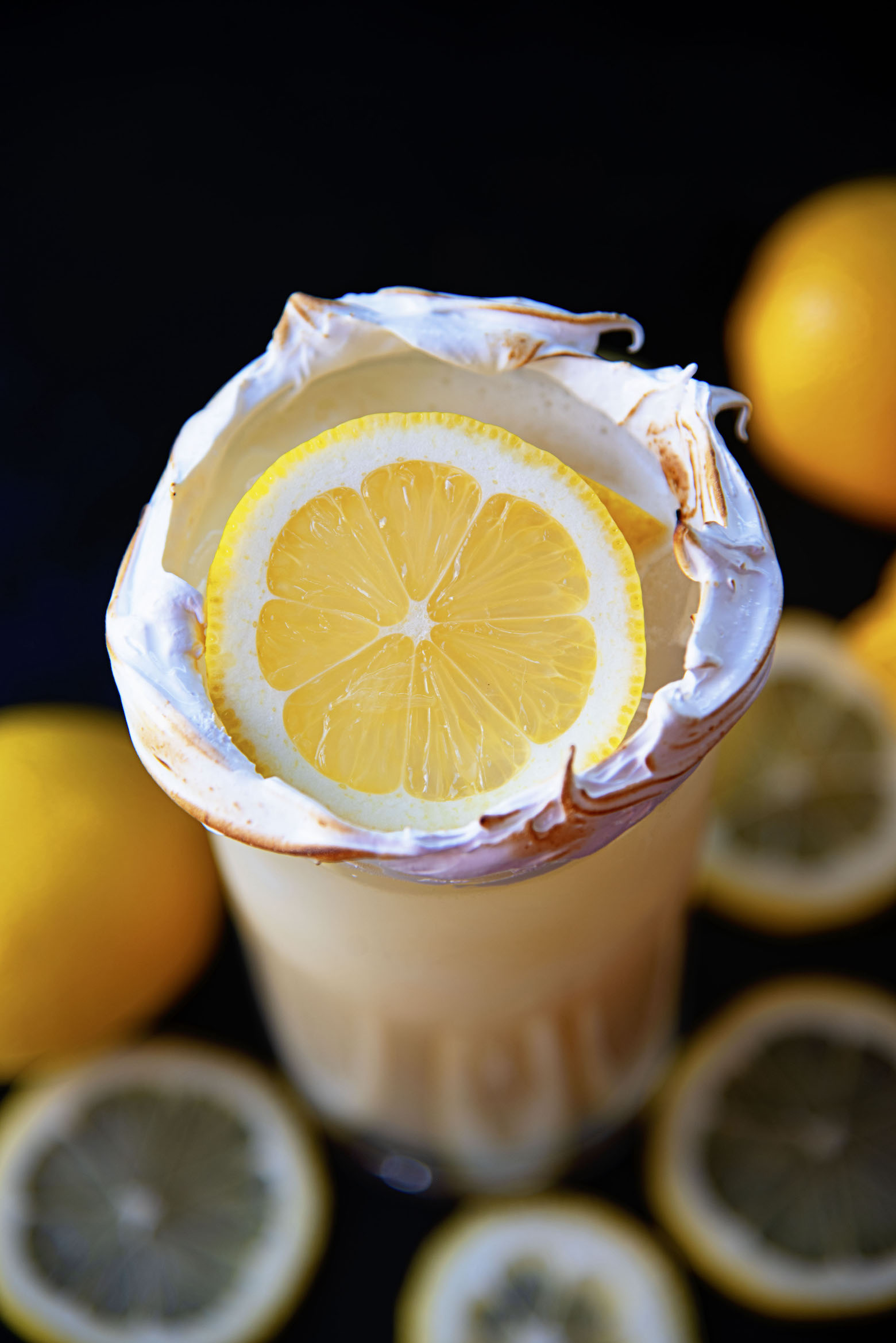 Overhead shot of cocktail with an up close shot of the lemon and meringue around the glass.