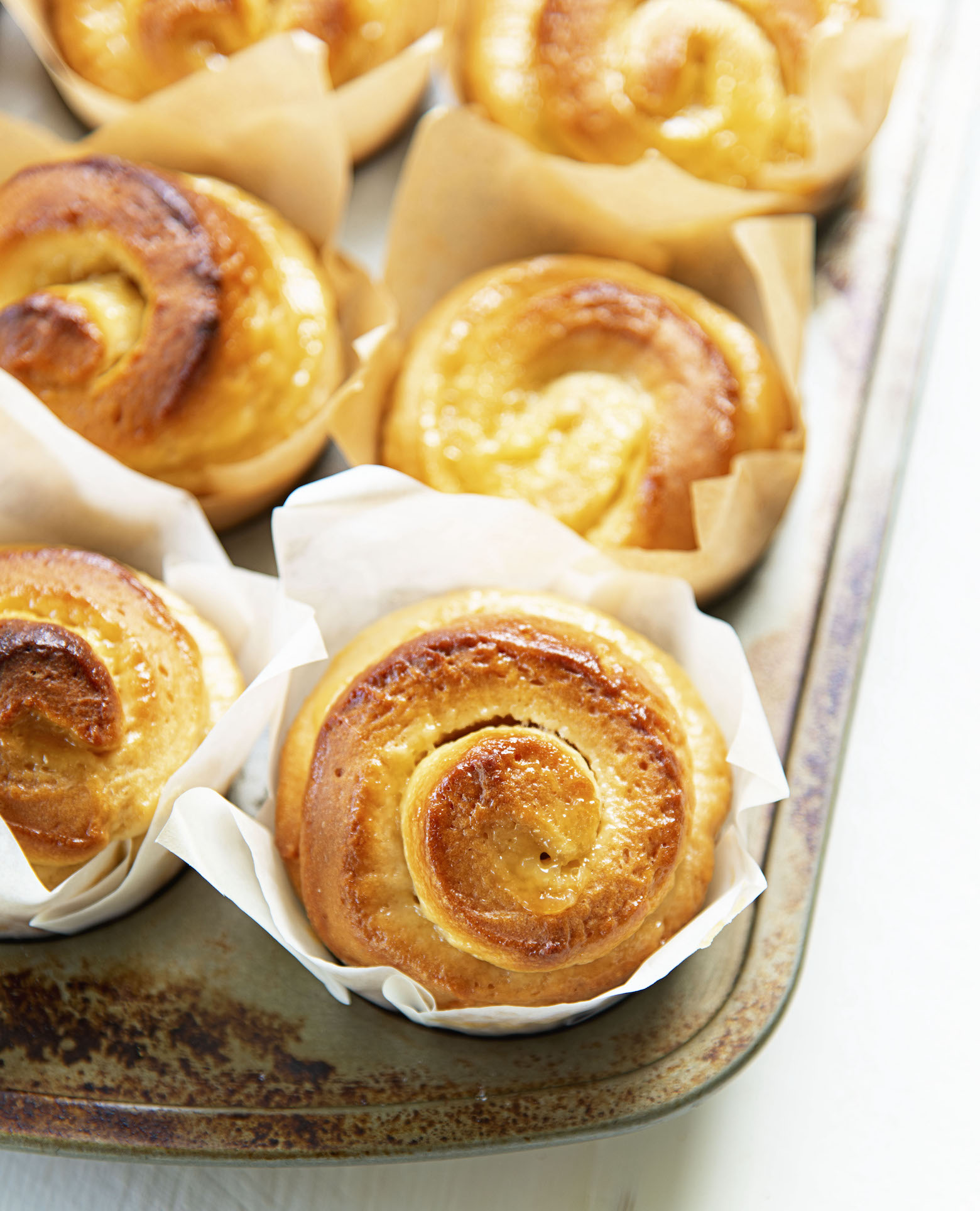 Picture of the rolls still in muffin pan showing the swirls of lemon curd.