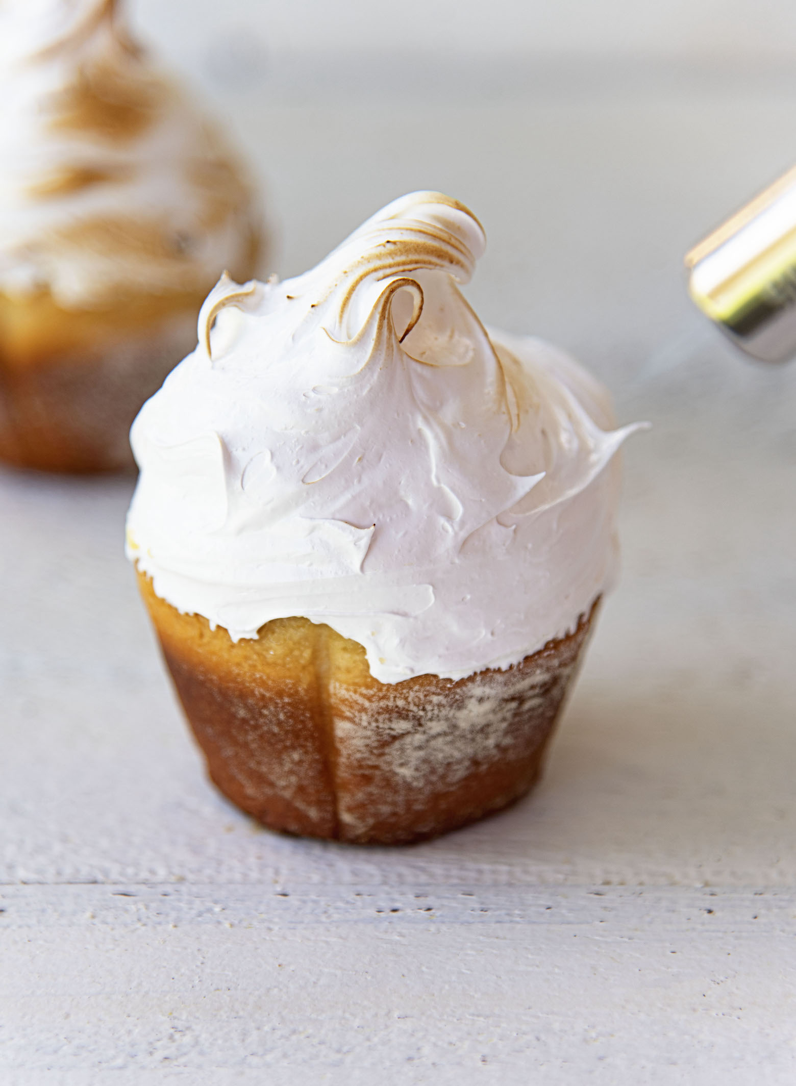 Picture of meringue covered sweet roll with blowtorch toasting the meringue.