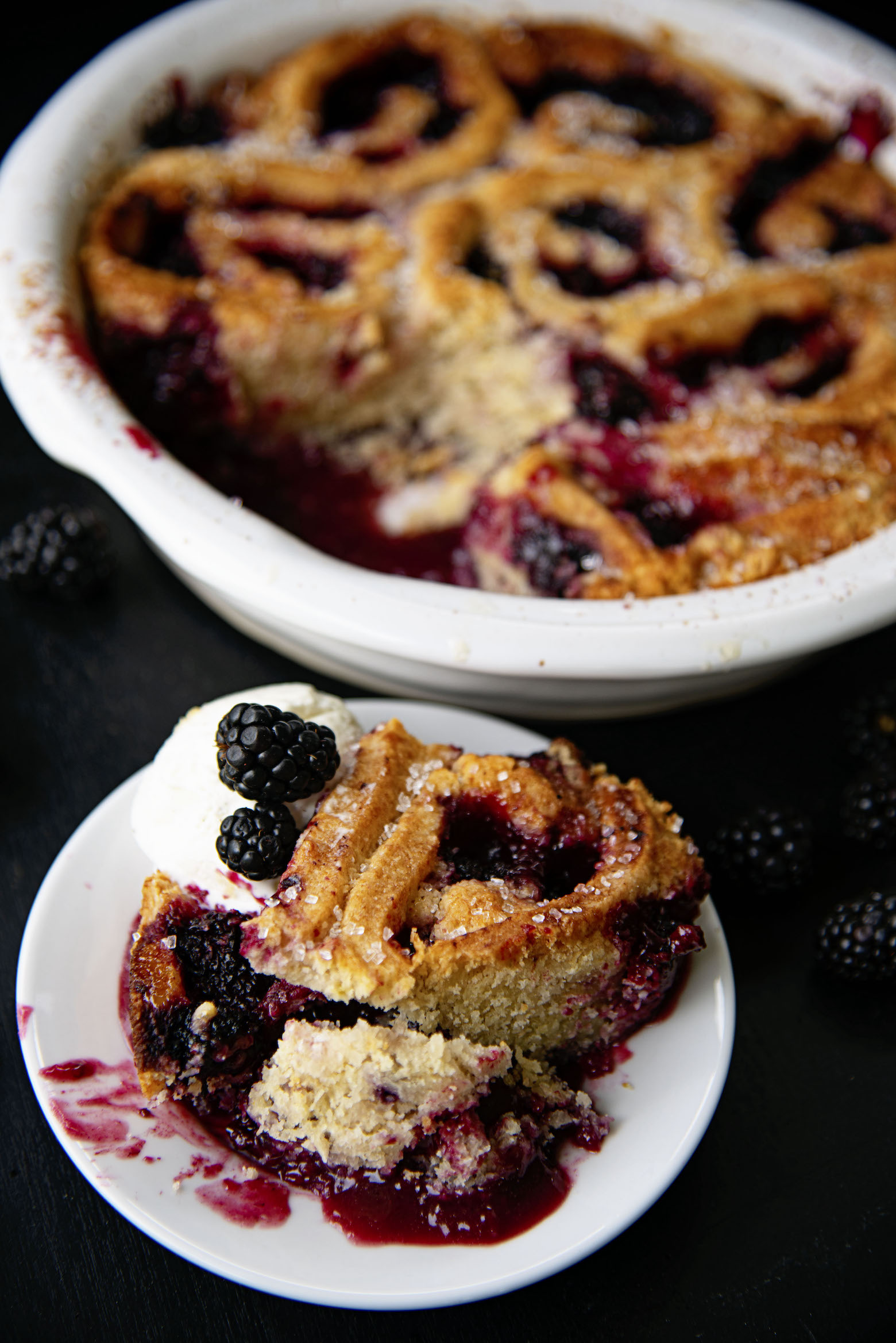 Cobbler on a plate with remaining cobbler in background.
