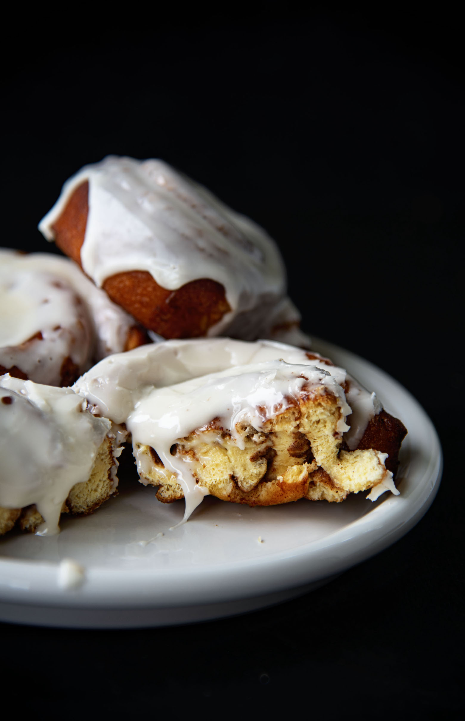 Deep Fried Cinnamon Rolls on a plate. One roll has a bite taken out of it.