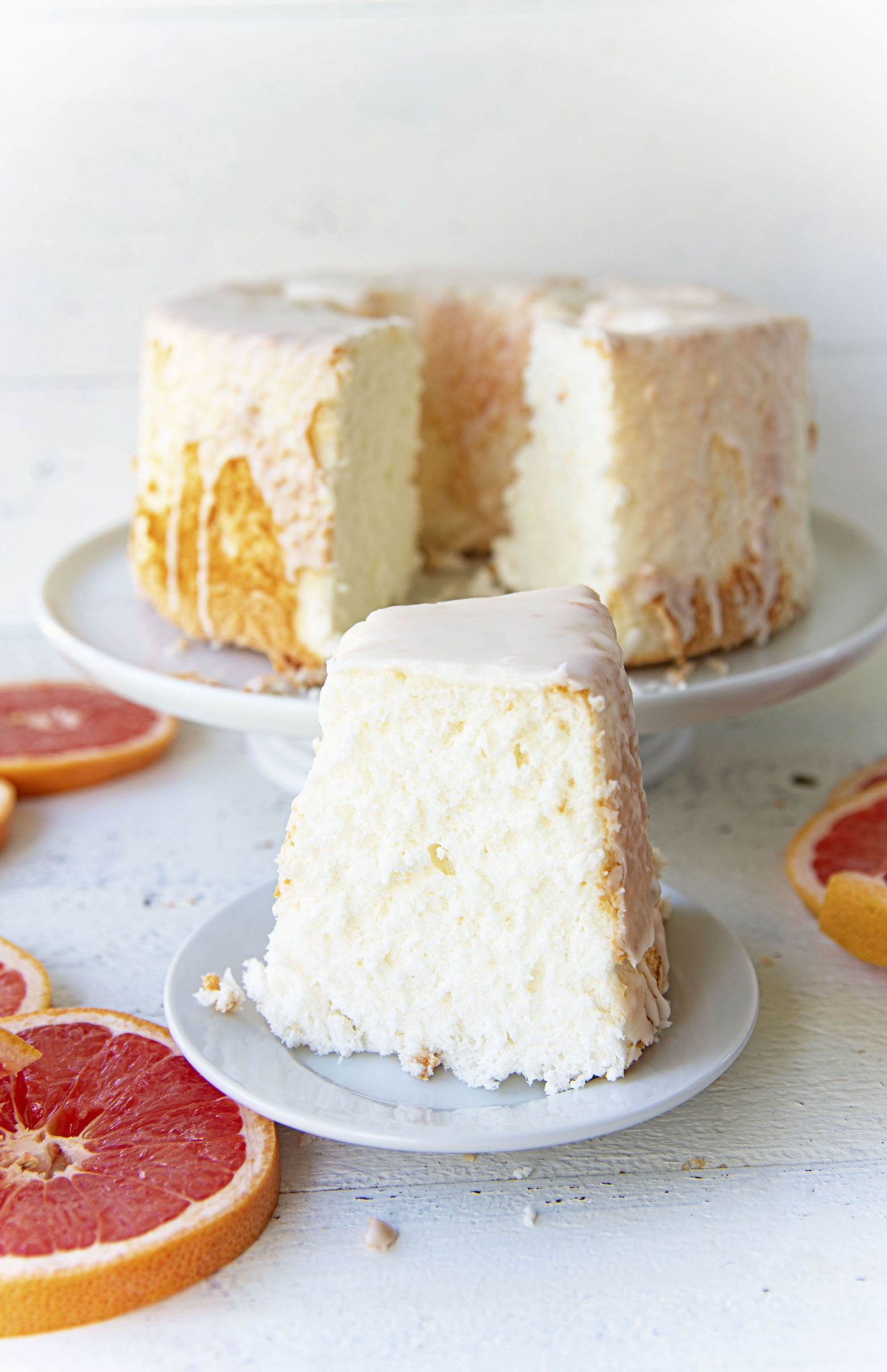 Side view of slice of Ruby Red Grapefruit Glazed Angel Food Cake with cake in background.